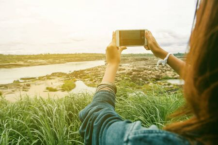 Taking a picture of an Asian woman with her cellphone, Outdoor atmosphere.focus on hand