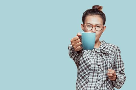 Asian woman holding a blue hot cup On a blue background,vintage style .Focus on hands