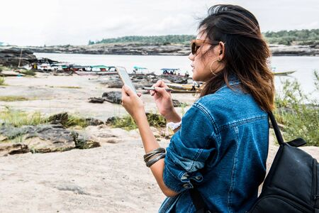 Asian women have used maps from a mobile phone.Focus on hand Banco de Imagens