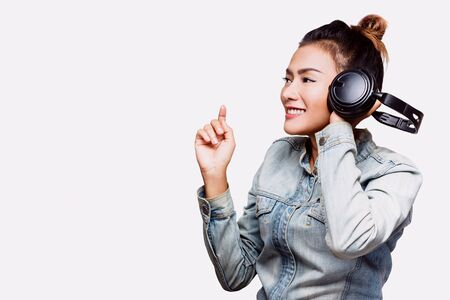 Asian women are using headphones happily. Focus on face