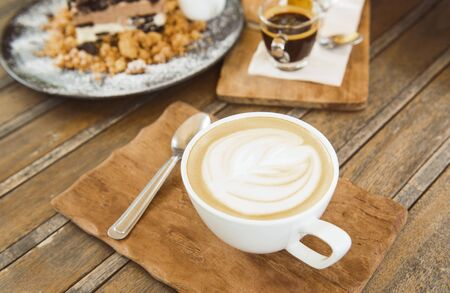 Picture of coffee cup And pastries placed on a vintage style wooden table.focus on cup