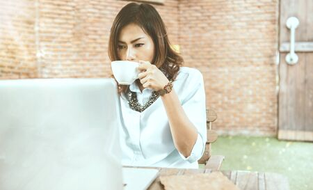 Quiet atmosphere Asian women sitting and drinking coffee in cafes Happy and relaxed emotions.Focus on  hand