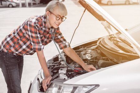 An Asian woman is opening the hood to check the condition of the car. Before her departure.Fcus on face Banco de Imagens