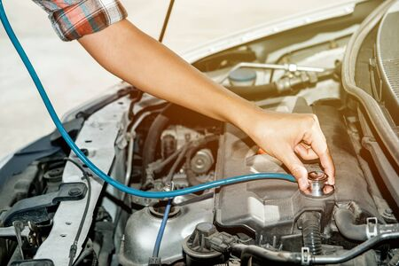 The hands of an Asian woman are checking her engine symptoms before traveling.Focus on hand