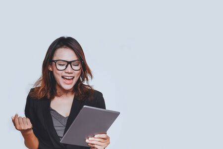 Asian woman smiled in a happy mood as she stared at her tablet on white background Banco de Imagens