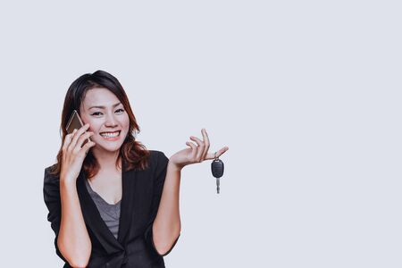 Asian woman smiled when she held the car key on  white background.