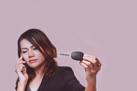 Asian woman regret when holding her car key on  background.Focus on car key