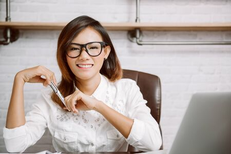 Smiling Asian woman sitting in the office, at home, happy mood.Focus on face