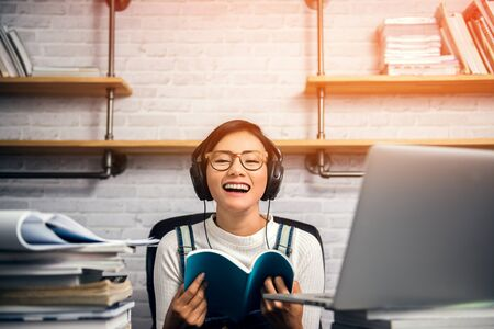 Pictures of an Asian woman smiling and reading in her room.Focus on face Banco de Imagens