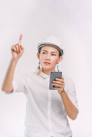 Asian women are standing and using video calls, with the intent on white background. Focus on face