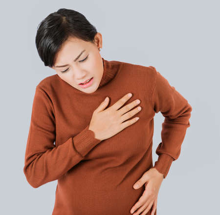 Pregnant  asia women Use the hand to grasp her chest and feel pain in the chest area.Focus on face Zdjęcie Seryjne