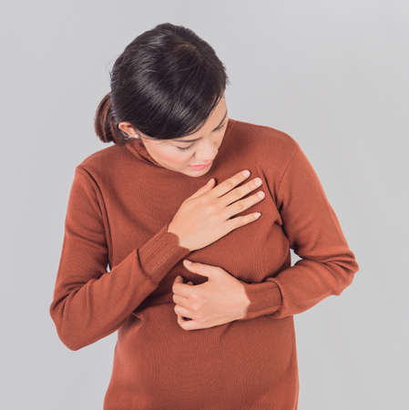 Pregnant  asia women Use the hand to grasp her chest and feel pain in the chest area.Focus on hand