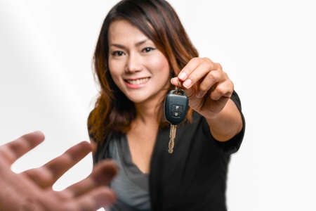 Smiling asian woman Handing over car keys to people In a happy. mood Focus on the keys Archivio Fotografico
