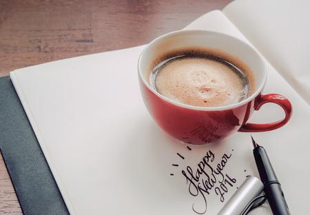 taza: Una taza de caf� que descansa sobre un libro con el texto feliz a�o nuevo 2016.Tone de la pen�nsula medida que la luz de la ma�ana Foto de archivo