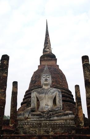 Buddha sit on ruins temple in Sukhothai historical park have stupa background photo