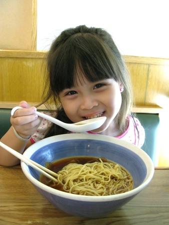 Asian young girl eating noodle Stock Photo - 9325234
