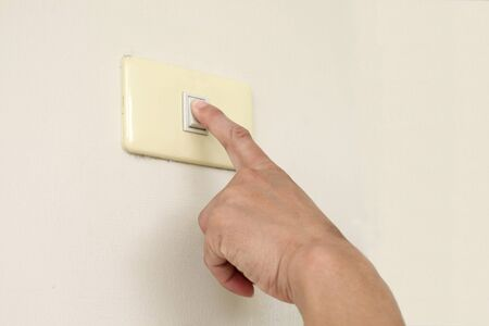 Finger turning off or turning on the wall-mounted light switch photo