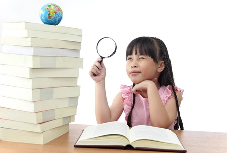 Student little girl reading with magnifying glass watch the globe.