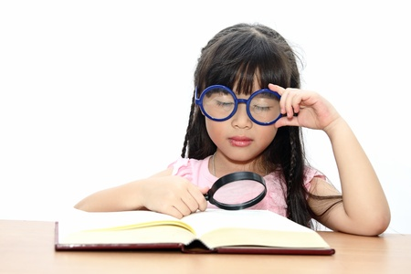 Student little girl reading with magnifying glass photo