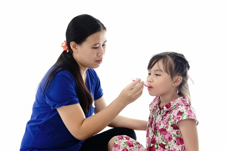 take medicine: Girl takes medicine from mother Stock Photo