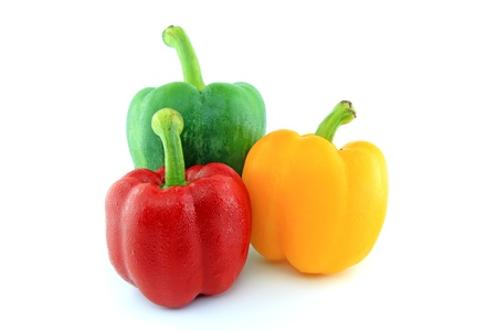 capsicum: Green Red Yellow paprika peppers with water drops isolated on white background
