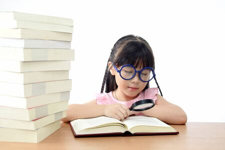 Student little girl reading book with magnifying glass  photo
