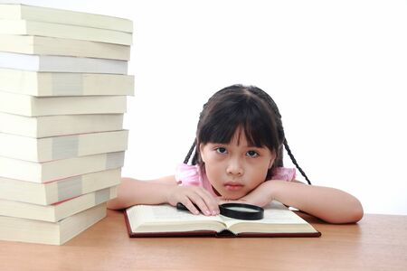 Beautiful little and serious asian girl reading book. photo