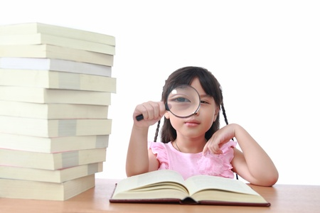 Asian little girl reading a book with magnifying glass isolated on a over white background photo