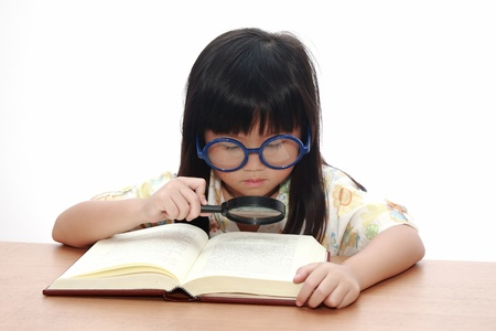 asian school girl: Asian little girl reading a book with magnifying glass isolated on a over white background Stock Photo
