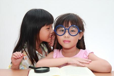 Cute little asian girl whispering something to her sister photo