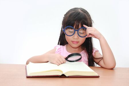 Happy little asian girl reading book wearing blue glasses, back to school concept, isolated over white  photo