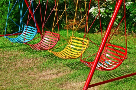 girl on swing: Colorful swing hanging in garden