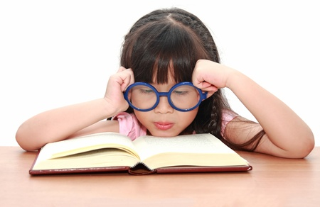 Asian little girl reading a book isolated on a over white background photo