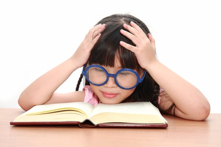 Asian little girl reading a book isolated on a over white background Stock Photo - 11064690