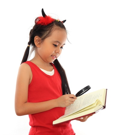 Beautiful little asian girl reading book with magnifying glass photo