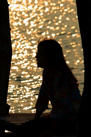 single adult woman silhouette with sea background photo