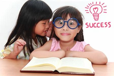 telling: Cute little asian girl whispering something to her sister Stock Photo