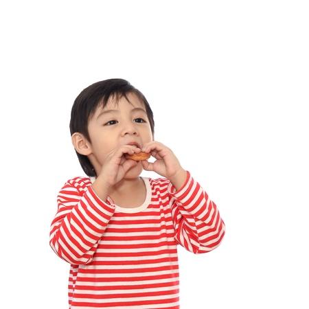 Little cute kid eating eating cookie photo