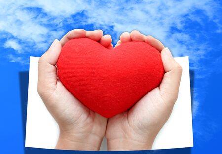 devotions: Red heart symbol on hands blue sky background