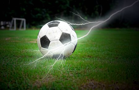 Football on green grass with lightning photo