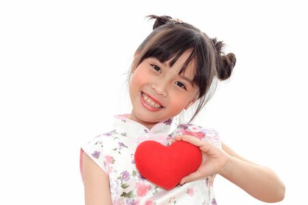 Adorable Chinese little girl holding red heart. photo