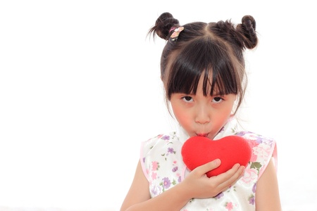Adorable Chinese little girl kissing red heart photo