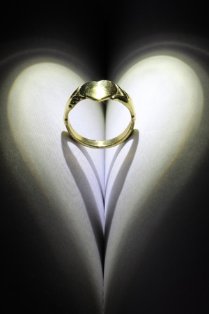 verse: Golden heart ring casting a heart shaped shadow.