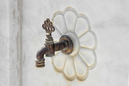 bronze bowl: Antique faucets  Stock Photo