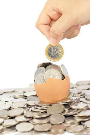 hand keep euro coin on broken eggshell Stock Photo - 12602405