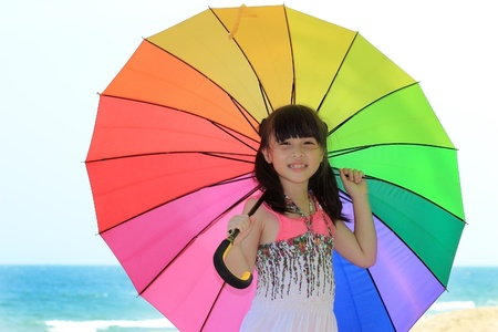 Girl with colorful umbrella on the sandy beach photo