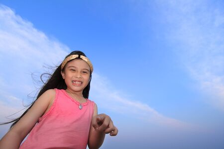 Happy asian girl having fun with sky background photo