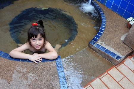 Adorable girl in hot spring water pool photo