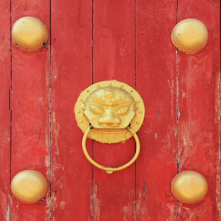 Golden Dragon knock on old red wooden door photo