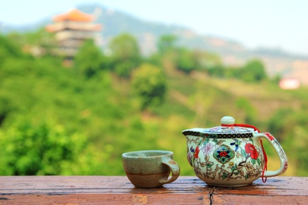 Teapot and cup set against the lush green hill background photo